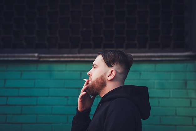 Cigarro de fumo de homem bonito
