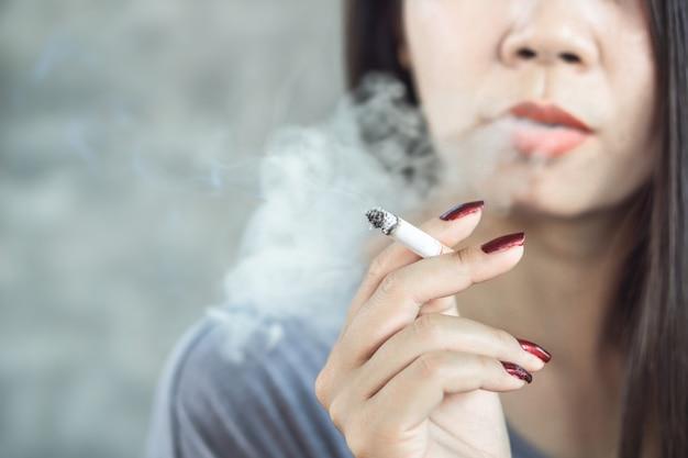 Cigarro de fumo de mão de mulher asiática