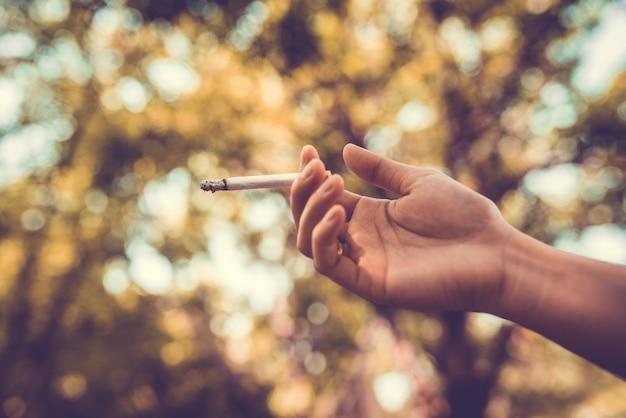 Cigarro de fumo do homem novo no parque ou na natureza verde.