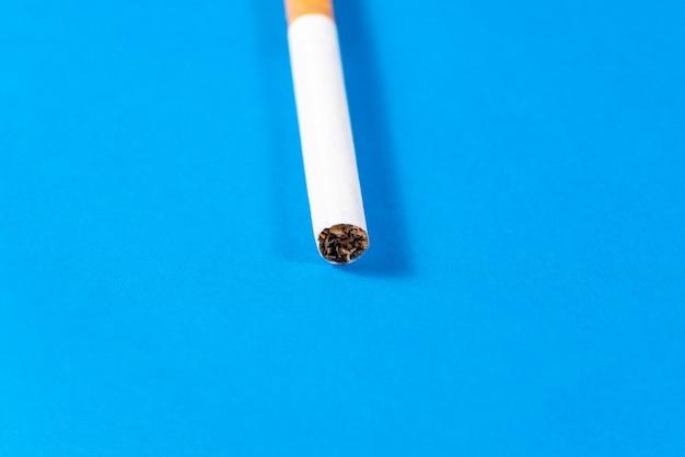 Cigarro de tabaco perto com fundo azul