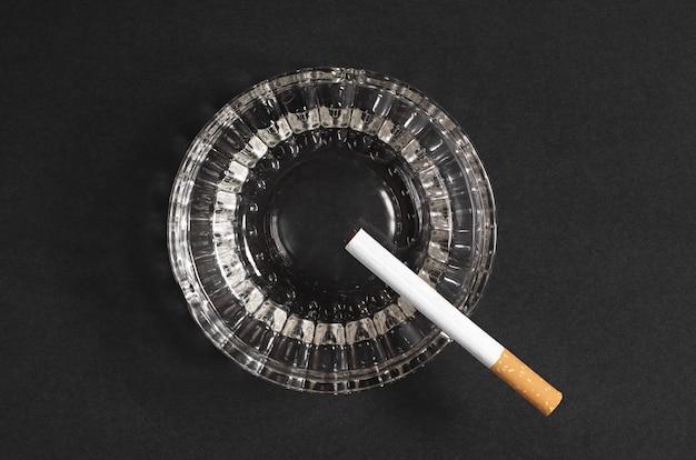 Cigarro e cinzeiro em fundo preto, vista superior