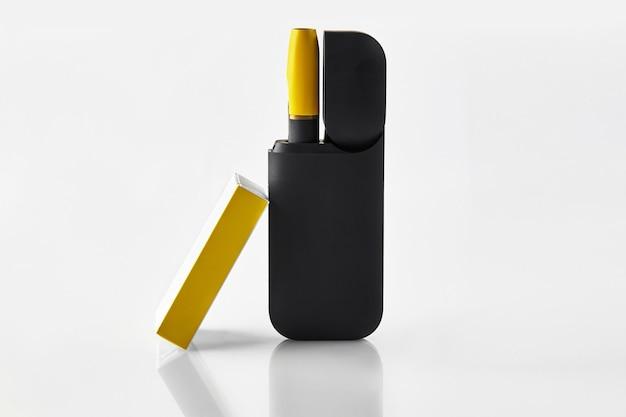 Cigarro eletrônico preto e amarelo de nova geração com bateria aberta e caixa de fósforos isolada no branco ...