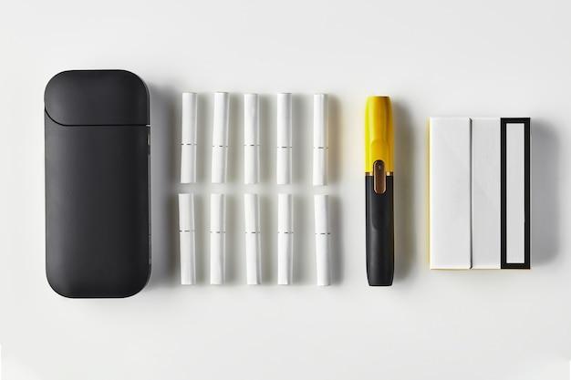 Cigarro eletrônico preto e amarelo de nova geração e bateria com um pacote e dez heatsticks isolados ... Foto Premium