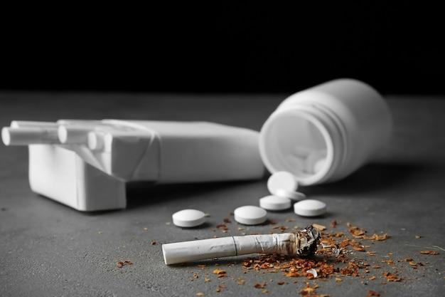 Cigarro, maço e comprimidos danificados na mesa cinza