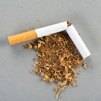 Cigarro quebrado com tabaco, tabaco se espalhando pela mesa cinza