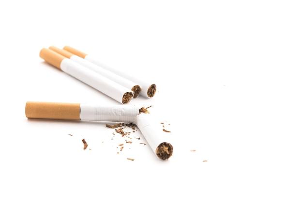 Cigarro quebrado e tabaco isolado em background branco
