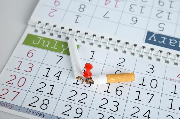 Cigarro quebrado preso ao calendário, close