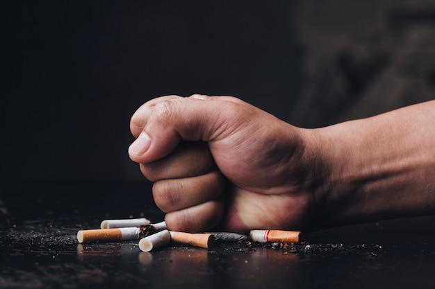 Cigarros de destruição da mão masculina no fundo preto. pare de fumar. dia mundial sem tabaco