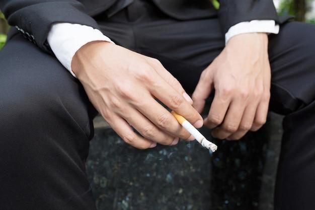 Cigarros de empresários para fumar sentados no parque