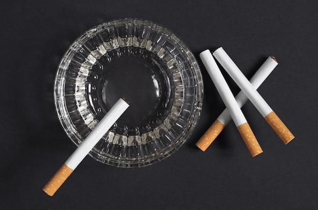 Cigarros e cinzeiro em fundo preto, vista de cima