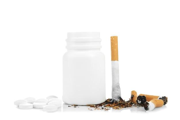 Cigarros e comprimidos danificados isolados no branco