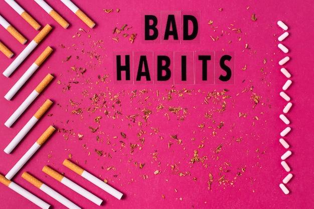 Cigarros e comprimidos em fundo rosa