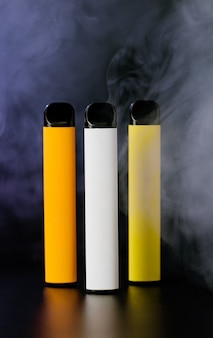 Cigarros eletrônicos descartáveis coloridos em preto com fumaça