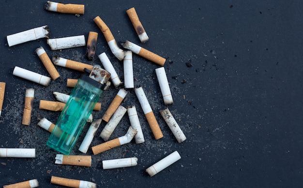 Cigarros fumados em fundo escuro.