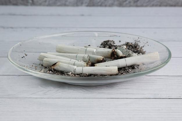 Cigarros fumados em um recipiente transparente. o conceito de danos à saúde. hábitos perniciosos