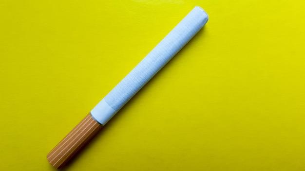 Cigarros isolados na diagonal em um fundo amarelo.