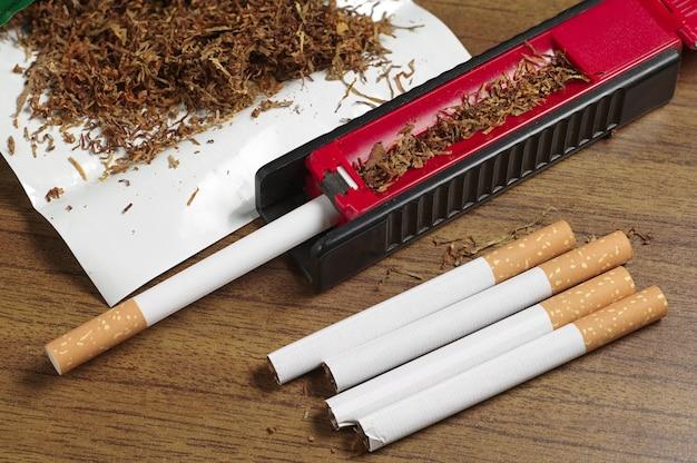 Cigarros, tabaco e máquina de enrolar na mesa