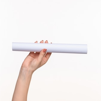 Cilindro branco dos adereços nas mãos femininas em fundo branco