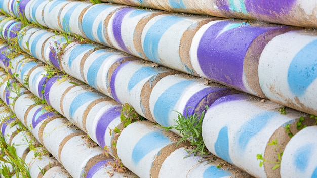 Cilindros de concreto formando uma parede colorida