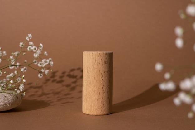 Cilindros de madeira e flores no fundo marrom pastel. pódios geométricos bons como forma para mostrar a vista lateral dos produtos