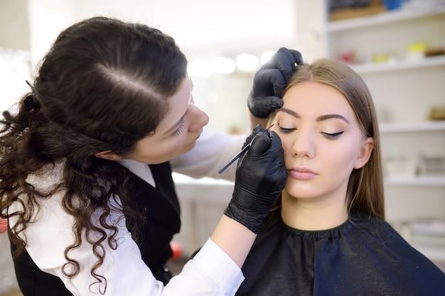 Cílios de olho de pintura esteticista pelo pincel. mulher atraente, recebendo cuidados faciais e maquiagem no salão de beleza. sobrancelhas de arquitetura.