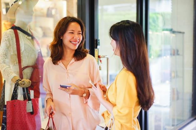 Cima, bonito, mulheres asian, segurando, saco, e, smartphone, enquanto, acabamento, shopping, em, centro comercial