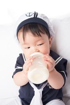 Cima, de, bebê asiático, criança, bebendo, mãe amamentando, de, garrafa