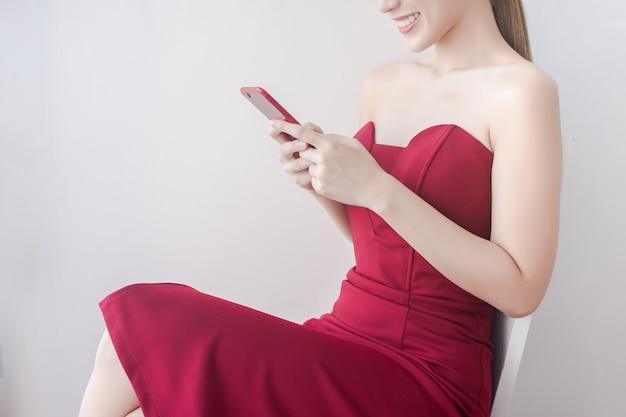 Cima, de, bonito, mulher asian, ligado, vestido vermelho, jogo, telefone vermelho, e, sorrizo