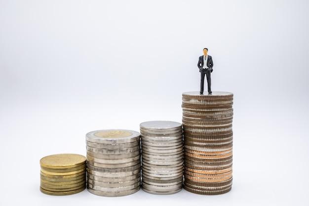Cima, de, homem negócios, miniatura, figuras, ficar, ligado, pilha moedas