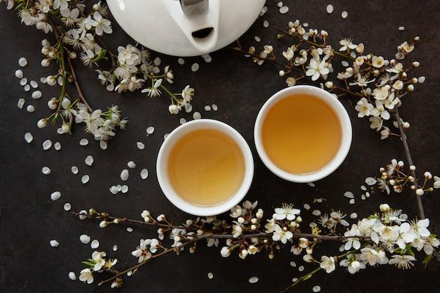 Cima, de, porcelana branca asiático, jogo chá, com, verde, japão chá, com, cereja, florescer ramos