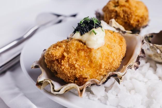 Cima, de, profundo, fritado, ostras, cobertura, com, maionese, e, caviar, servido, em, prato branco