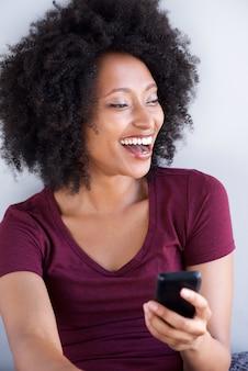 Cima, jovem, mulher preta, rir, com, telefone móvel