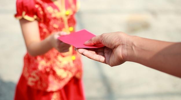 Cima, mão, dê dinheiro, em, vermelho, envolva, para, menina, ligado, chinês, ano novo