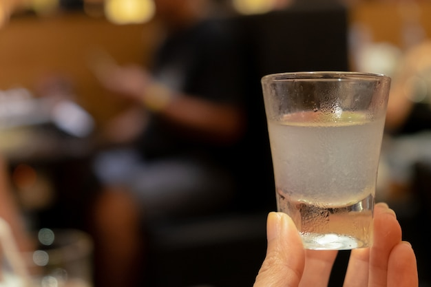 Cima, mão, segurando, limão, coquetel, bebida, em, pequeno, copo vidro, com, obscurecido, junte tabela, fundo
