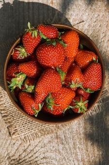 Cima para baixo tiro de tigela de barro cheio de morangos maduros vermelhos.