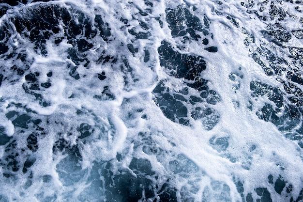 Cima para baixo vista aérea da superfície da água do mar. textura de ondas de espuma branca como parede natural.