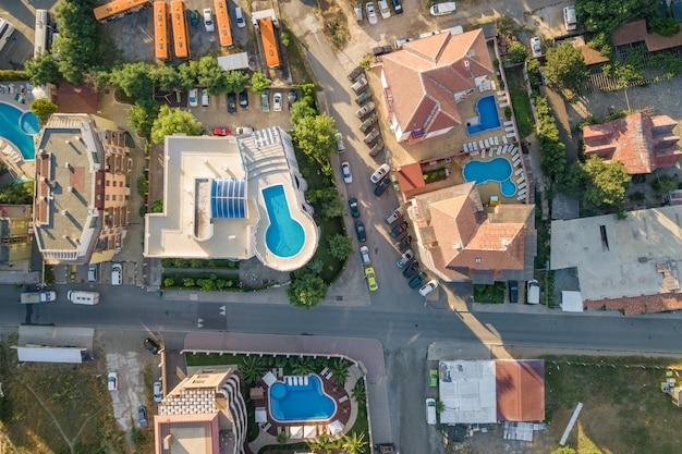 Cima para baixo vista aérea de telhados de hotéis, ruas com carros estacionados e piscinas com água azul na cidade resort, perto do mar.