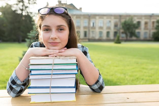 Cima, retrato, de, highschool, menina, descansar, cabeça, ligado, livros