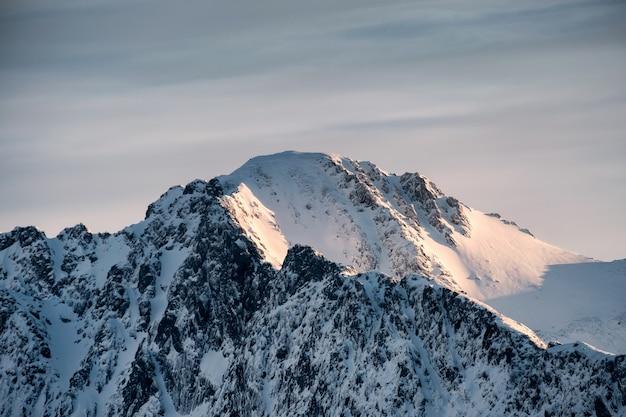 Cimeira da montanha de neve com o nascer do sol brilhando