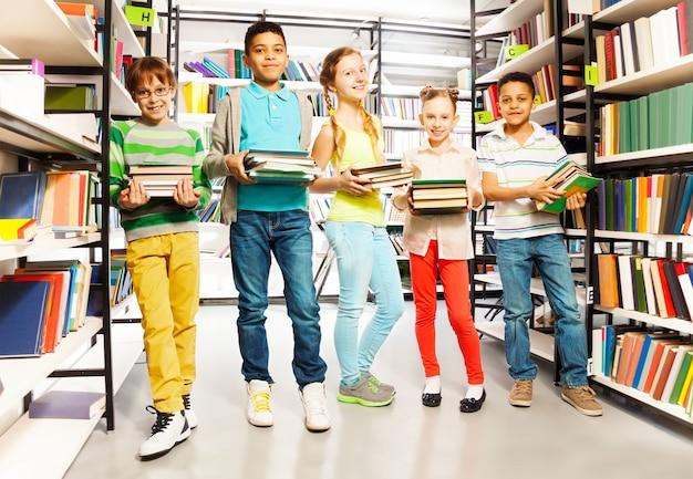 Cinco amigos com pilhas de livros na biblioteca em pé em uma fileira e sorrindo
