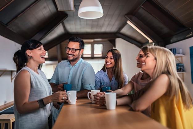 Cinco amigos rindo enquanto bebe chá ou café na mesa do contador.