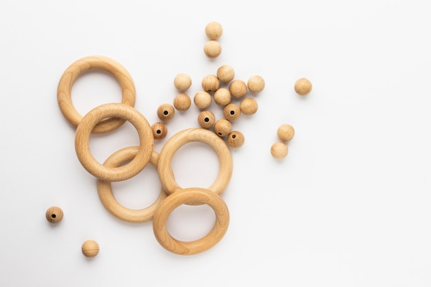 Cinco anéis de madeira e miçangas em fundo branco. mordedor de bebê em madeira natural. brinquedo infantil ecológico. vista superior, plana com espaço de cópia.