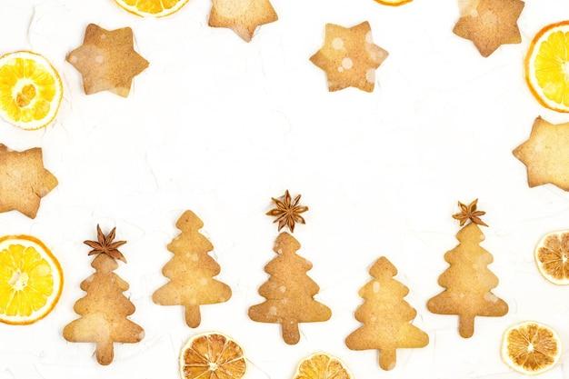 Cinco biscoitos de árvore de natal com chapéus de coco estrela e laranja seca em fundo branco com copyspace. bokeh tonificado e neve