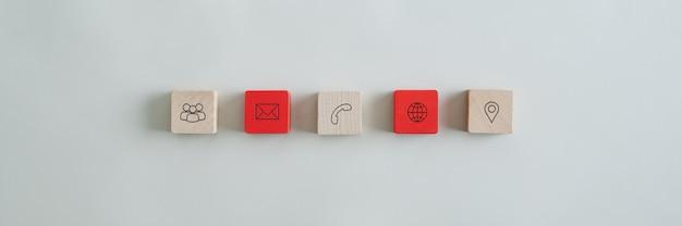 Cinco blocos de madeira com ícones de contato e informação