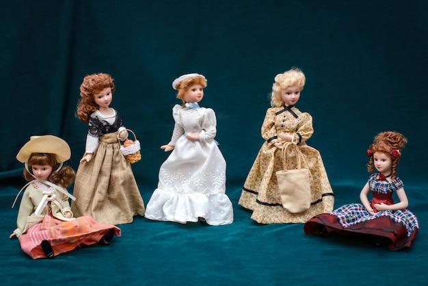 Cinco bonecas em vestidos vintage clássicos e chapéus no escuro