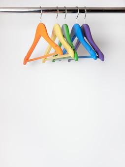 Cinco cabides vazios multicoloridos pendurados no guarda-roupa