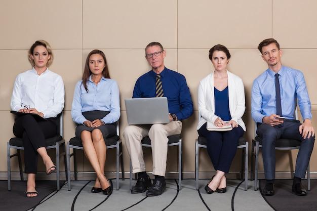 Cinco candidatos sérios sentam-se na sala de espera