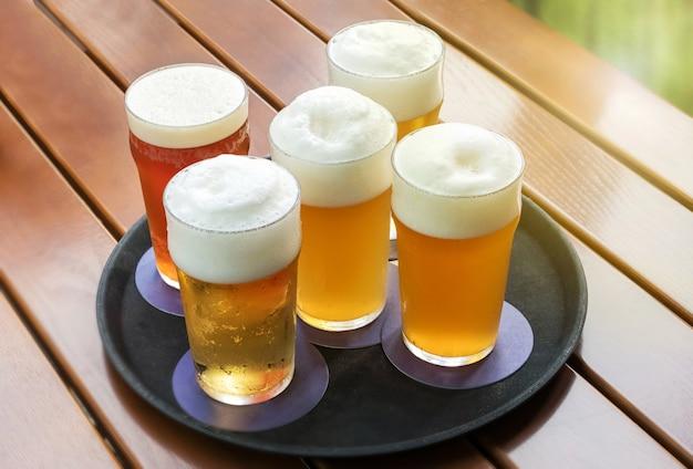 Cinco cervejas geladas com espumas em copos em uma bandeja em uma mesa externa de ripas em um ângulo alto de vista de perto