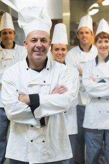 Cinco chefs usando uniformes enquanto levantam uma cozinha