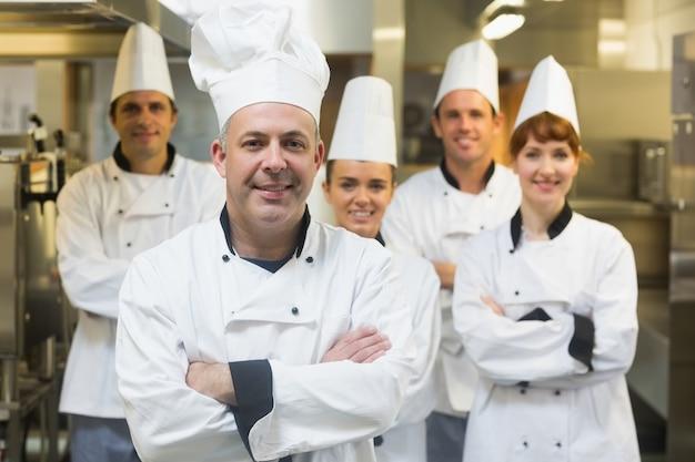 Cinco chefs usando uniformes posando em uma cozinha